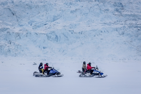Snowmobile Along A Glacier Wall